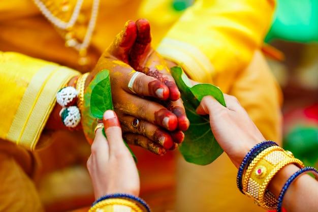 Indische traditionelle hochzeit bräutigam hand in haldi-zeremonie
