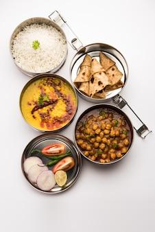 Indische vegetarische lunchbox oder tiffin aus edelstahl für büro oder arbeitsplatz, beinhaltet dal fry, chole masala, reis mit chapati und salat