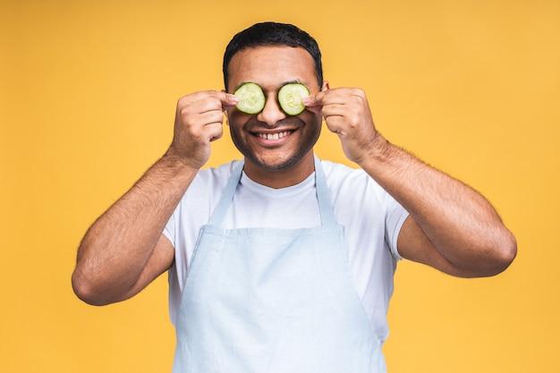 Indischer afroamerikanischer junger mann, der gurkenscheiben über den augen hält und lächelt oder lacht. getrennt über gelbem hintergrund. kochen sie die zubereitung von speisen.