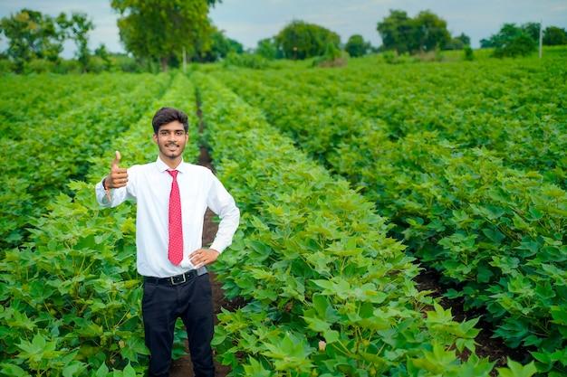Indischer agronom am baumwollfeld und zeigt schlag auf