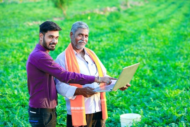 Indischer agronom mit landwirt am feld
