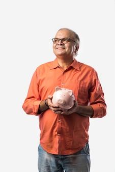 Indischer alter mann oder pensionierter älterer männlicher erwachsener mit sparschwein oder spardose