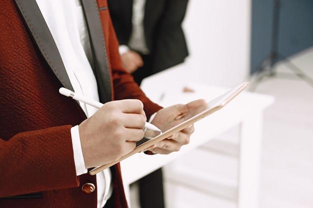 Indischer anwalt oder leitender angestellter, der notizen auf tablette macht.