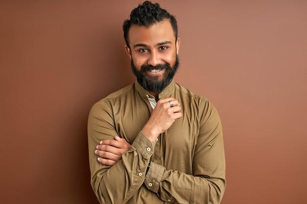 Indischer araber mit einem glücklichen und kühlen lächeln auf gesicht lokalisiert auf braunem o hintergrund