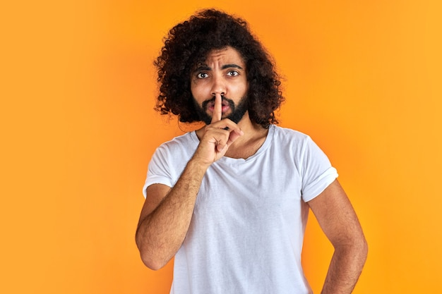 Indischer arabischer mann, der bittet, mit finger auf lippen, stille und geheimem konzept ruhig zu sein