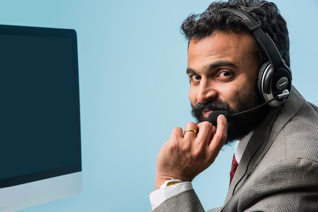 Indischer asiatischer bärtiger junger mann im anzug im callcenter, drinnen, kopfhörer hören, computer surfen oder einen sprachanruf führen having