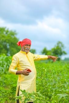 Indischer asiatischer bauer, der im landwirtschaftsfeld steht