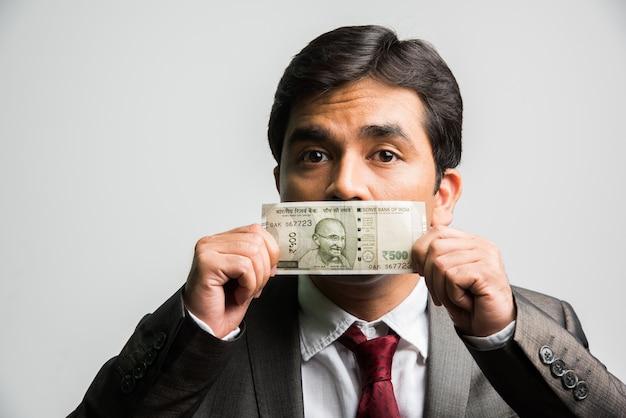 Indischer asiatischer geschäftsmann, der geldschein für mund oder gesicht hält