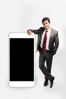 Indischer asiatischer geschäftsmann, der hand über großem smartphone ruht und in pose präsentiert, isoliert auf weißem hintergrund