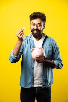 Indischer asiatischer junger bärtiger mann, der sparschwein auf gelb hält. menschen- und finanzkonzept Premium Fotos