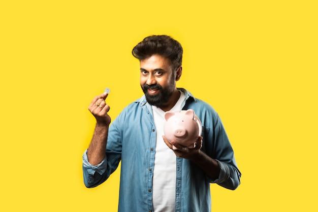 Indischer asiatischer junger bärtiger mann, der sparschwein auf gelb hält. menschen- und finanzkonzept