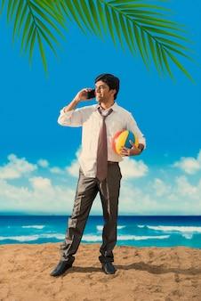Indischer asiatischer junger geschäftsmann, der sich vom strand entspannt oder arbeitet und eine pause von der arbeit genießt?