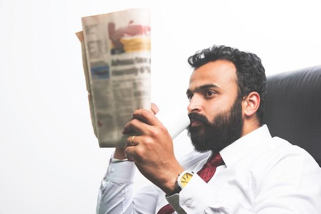 Indischer asiatischer junger geschäftsmann, der zeitung liest, während er kaffee am schreibtisch trinkt