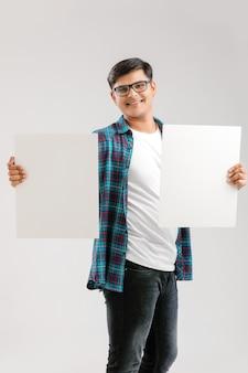 Indischer / asiatischer junger mann, der leeres schild auf weiß zeigt