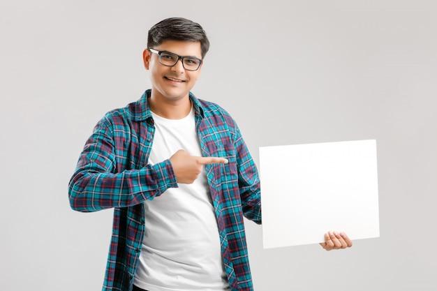 Indischer, asiatischer junger mann, der leeres schild zeigt