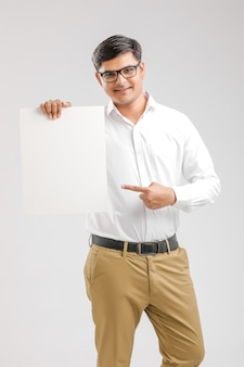 Indischer asiatischer junger mann, der leeres schild zeigt