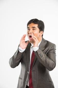 Indischer asiatischer junger und gutaussehender geschäftsmann, der in bürokleidung stehend laut schreit, isoliert auf weißem hintergrund