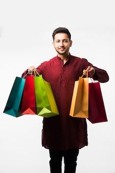 Indischer asiatischer mann in ethnischer kleidung mit einkaufstüten, stehend isoliert auf weißem hintergrund