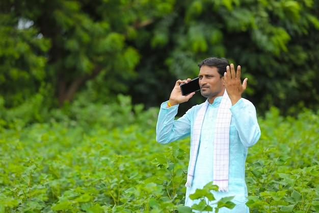 Indischer bauer, der auf dem grünen landwirtschaftsfeld mit dem smartphone spricht