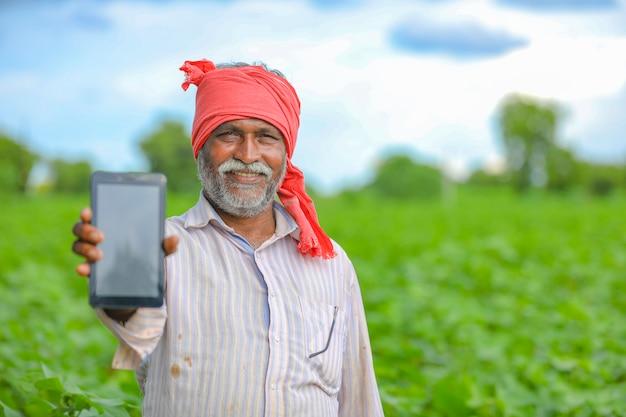 Indischer bauer, der einen mobilen bildschirm am landwirtschaftsfeld zeigt