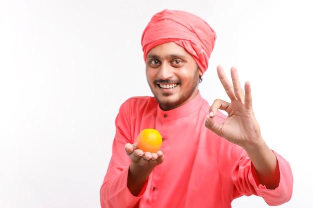 Indischer bauer, der in der hand eine orange frucht über weißem hintergrund hält.