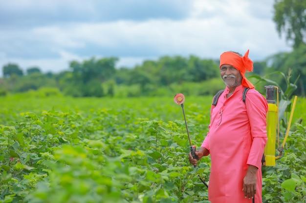Indischer bauer, der pestizid auf baumwollfeld sprüht
