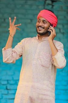 Indischer bauer, der zu hause am smartphone spricht.