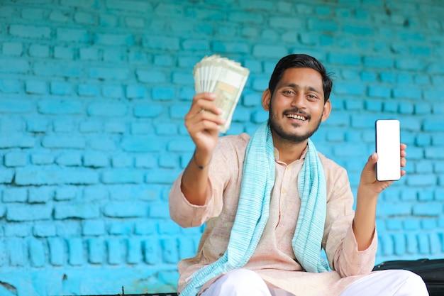 Indischer bauer, der zu hause smartphone und geld zeigt.