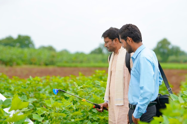 Indischer bauer im gespräch mit agronom bei farm und sammeln von informationen