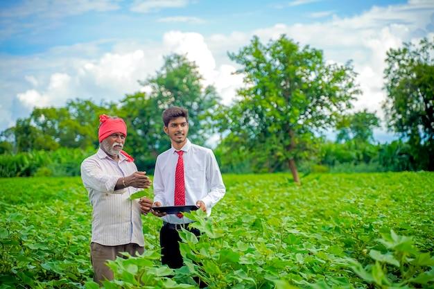 Indischer bauer mit agronom am baumwollfeld, der einige informationen auf der registerkarte zeigt