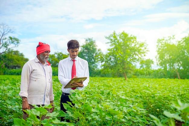Indischer bauer mit agronom am baumwollfeld und agronom, der einige informationen auf briefblock schreibt