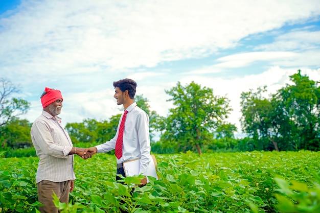 Indischer bauer mit agronom am baumwollfeld und händeschütteln