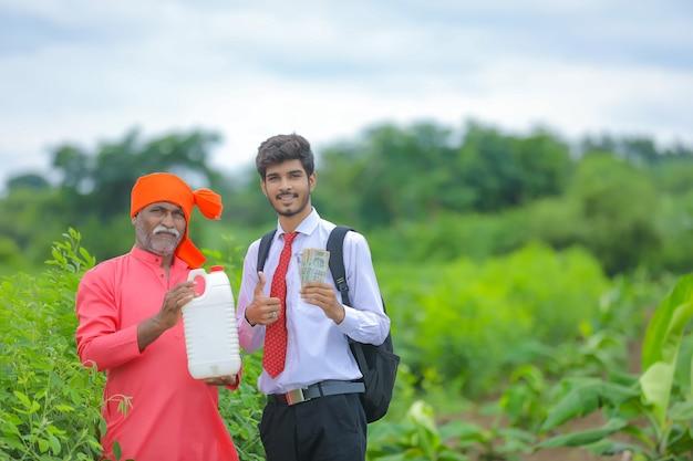 Indischer bauer mit agronom auf dem feld, bauer und agronom, der düngerflasche zeigt