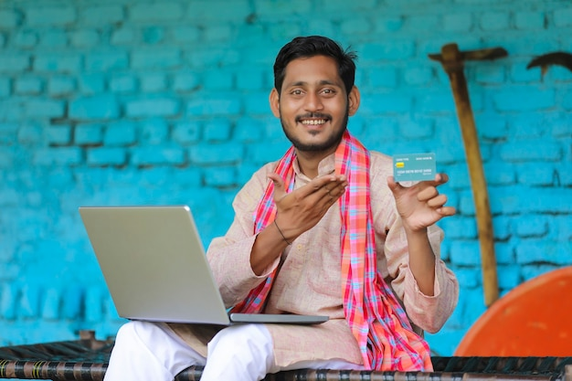 Indischer bauer mit laptop und karte zu hause.