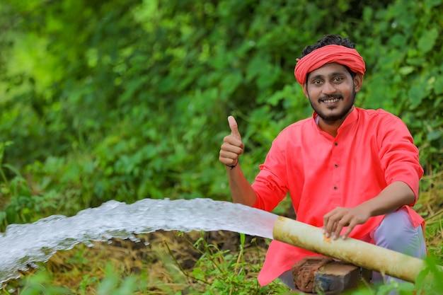 Indischer bauer mit wasserfluss vom rohr am feld