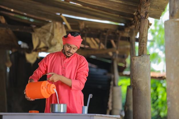 Indischer bauer oder milchmann, der milch auf milchfarm sammelt