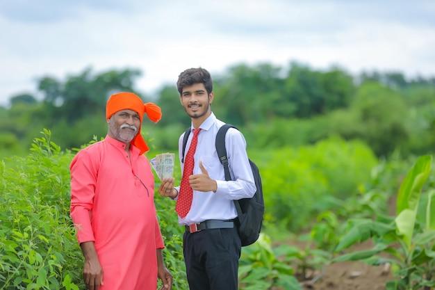 Indischer bauer und agronom, der indische rupie im feld zeigt