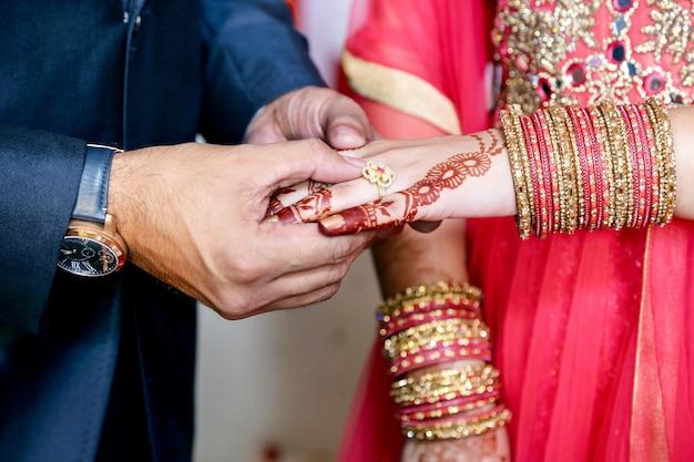 Indischer bräutigam, der ring auf indische braut setzt