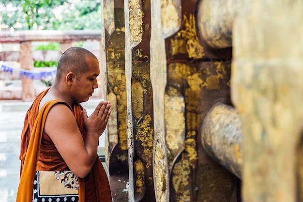Indischer buddhistischer mönch, der vor dem bodhi-baum nahe mahabodhi-tempel bei bodh gaya, bihar, indien steht und betet.