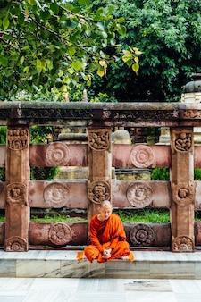 Indischer buddhistischer mönch in der meditation nahe dem bodhi-baum nahe mahabodhi-tempel.