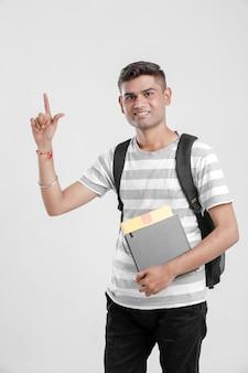 Indischer collegejunge, der tasche und bücher hält und richtung zeigt