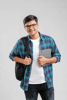 Indischer collegejunge, der tasche und tablette hält