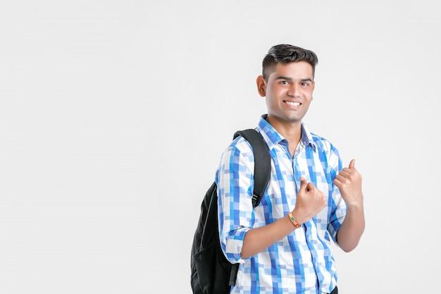 Indischer collegejunge mit dem halten der tasche und sich zeigen bums