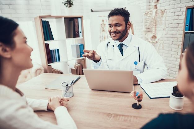 Indischer doktor, der patienten im büro sieht.