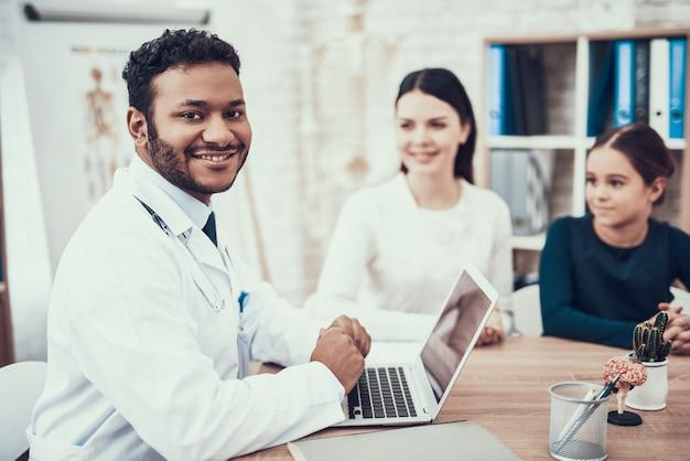 Indischer doktor im weißen kleid, das patienten im büro sieht