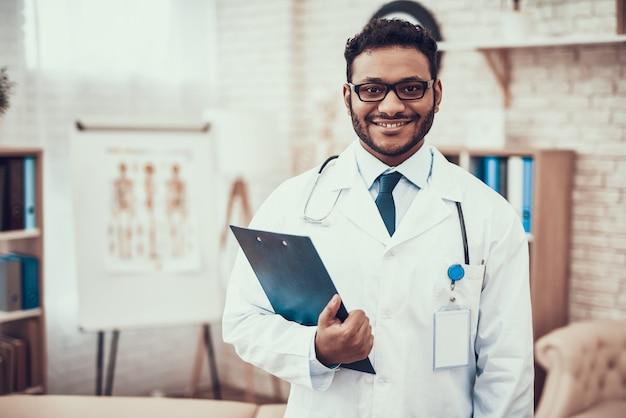 Indischer doktor mit stethoskop im krankenhauszimmer.