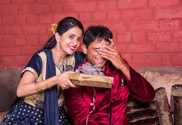 Indischer ehemann überrascht frau mit einem geschenk zu diwali oder jubiläum oder geburtstag, während er auf dem sofa sitzt