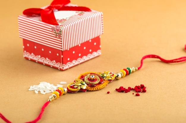 Indischer festival raksha bandhan hintergrund mit einem eleganten rakhi, reiskörnern und geschenkbox