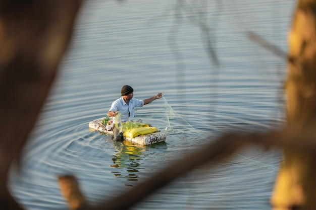 Indischer fischer, der im handgemachten boot fischt