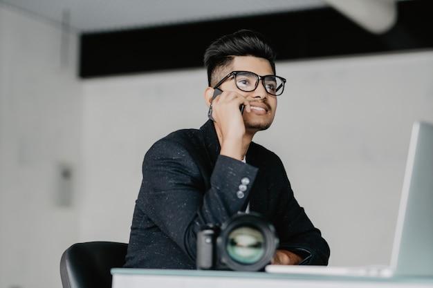 Indischer fotograf, der mit laptop im büro arbeitet und am telefon spricht